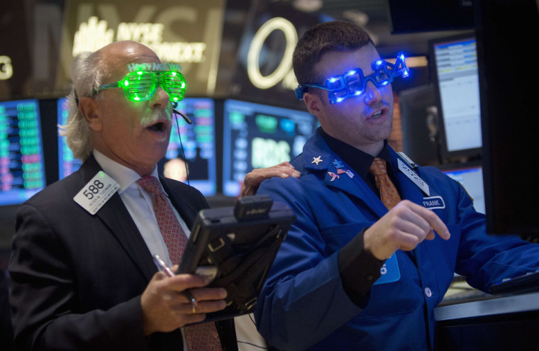 Traders, wearing novelty 2014 glasses, trade at the closing bell on the floor of the New York Stock Exchange on New Year's Eve in New York, December 3...