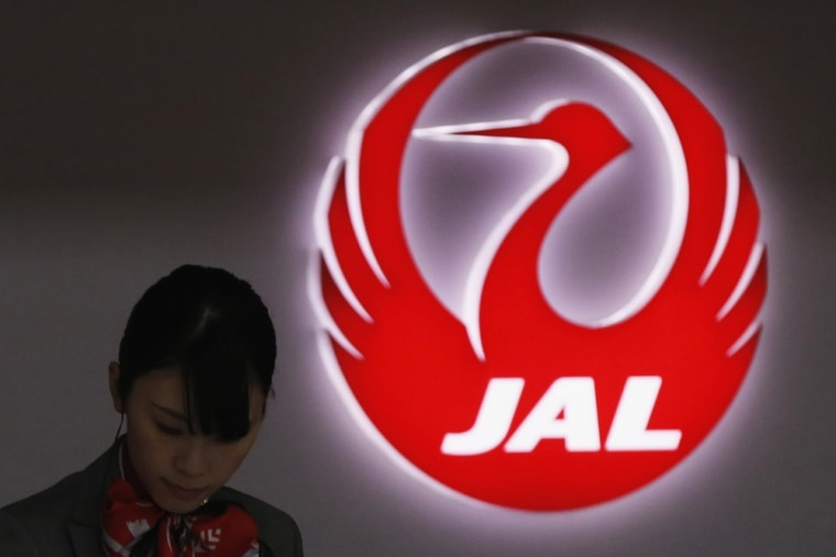 An employee of Japan Airlines works next to the company logo at Haneda Airport in Tokyo February 4, 2013.
