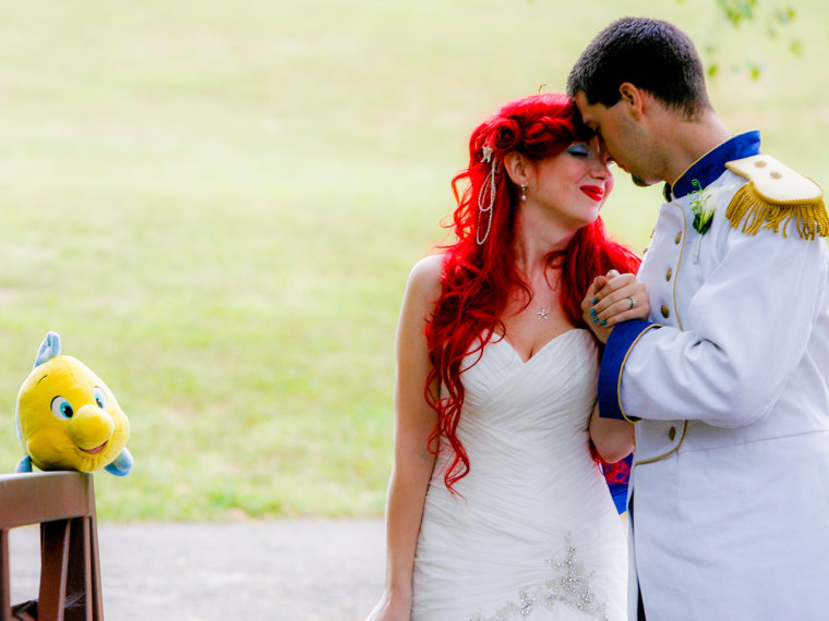 Jamie and Christopher Chandler, dressed as Princess Ariel and Prince Eric, prepare to exchange vows at their Disney-themed wedding.