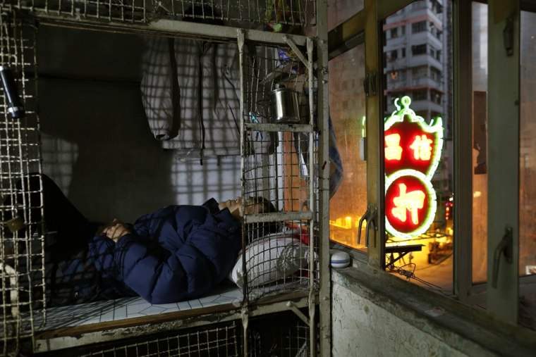 In this Jan. 25, 2013 photo, 62-year-old Cheng Man Wai lays in his cage, measuring 1.5 square meters (16 square feet), which he calls home, in Hong K...
