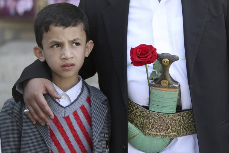 A boy looks on as he stands with his father with a rose placed on his belt while they shop for gifts on Valentine's Day in Sanaa, February 14, 2013. REUTERS/Mohamed al-Sayaghi (YEMEN - Tags: SOCIETY)