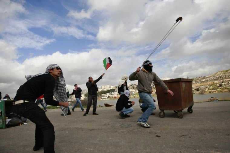 Palestinians throw rocks during clashes with Israeli troops outside Ofer military prison near the West Bank city of Ramallah on Friday. At least 16 people were injured as Israeli forces fired into the air and used rubber bullets.