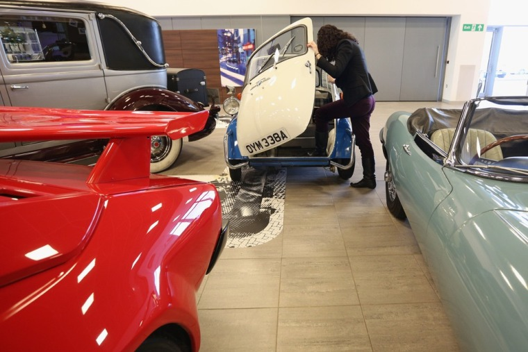 An employee of Bonhams auction house admires a 1959 BMW Isetta 300, which featured in the 'Important Motor Carts and Automobilia' auction on December ...
