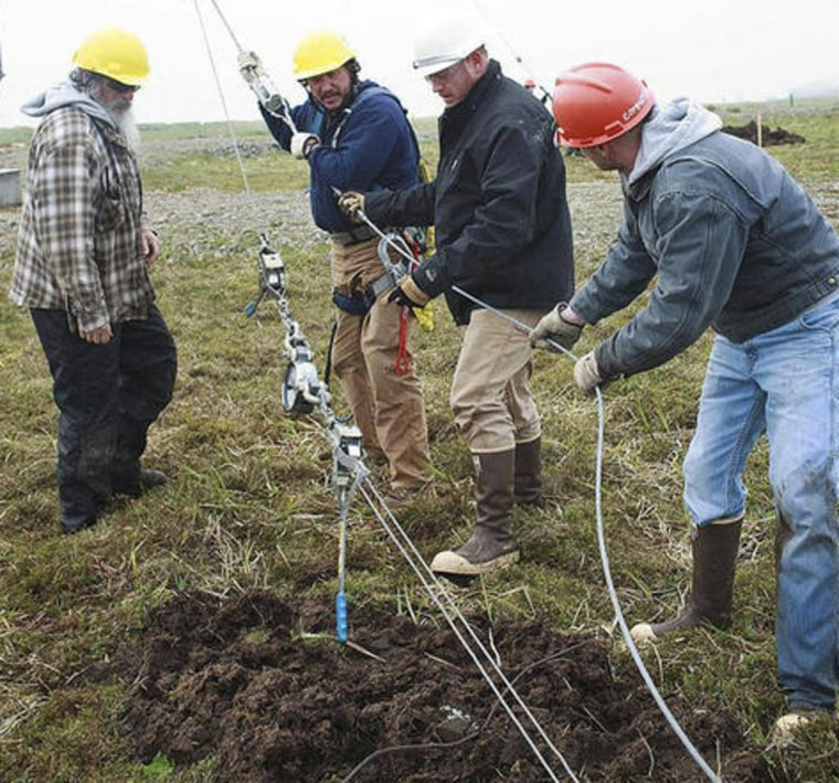 This July 2, 2011 photo provided by the U.S. Coast Guard shows Richard Belisle, second from left, and Coast Guard Petty Officer 1st Class James Hopkins, second from right, with Jim Wells, left, and Coast Guard Petty Officer 3rd Class Cody Beauford as they help erect a communications antenna on Shemya Island, Alaska. Belisle and Hopkins were slain in April 2012, and Wells reportedly has now been charged with their murders.