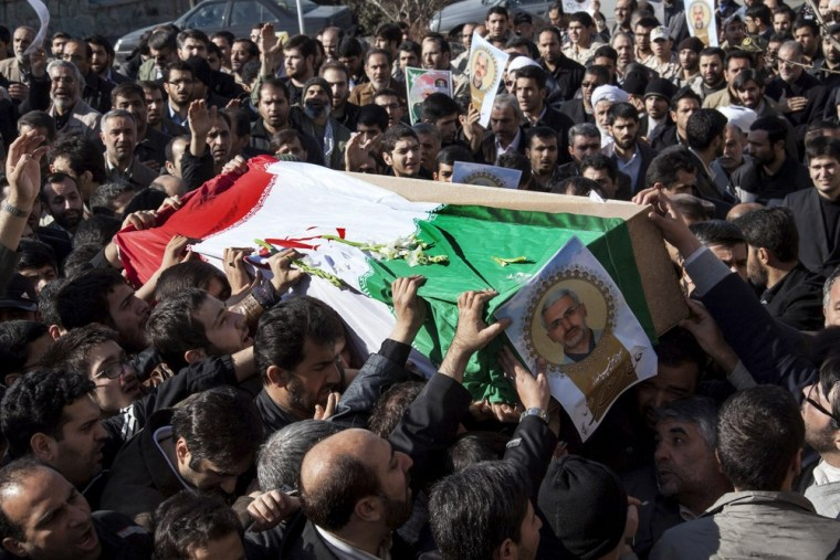 Iranian mourners carry the flag draped coffin of Hassan Shateri in Tehran, Thursday.