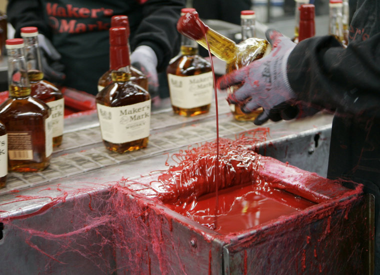 In this Wednesday, April 8, 2009 photo, a bottle of Maker's Mark bourbon is dipped in red wax during a tour of the distillery in Loretto, Ky.