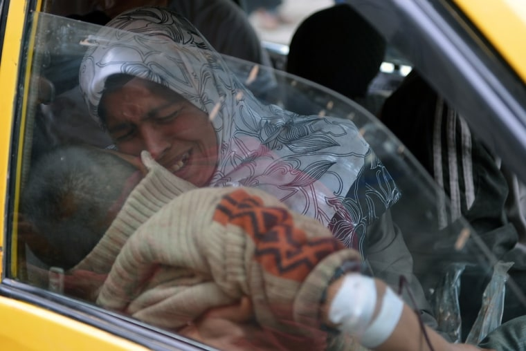 A Syrian woman hold her injured son in a taxi as they arrive at a hospital in Aleppo on Feb. 8.