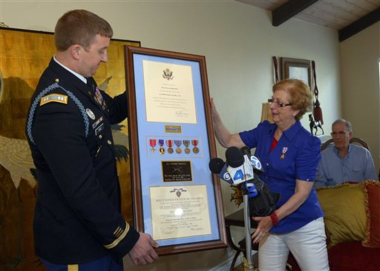 Army Capt. Zachariah L. Fike presents Hyla Merin with a plaque Sunday that contains medals presented posthumously to her father after they were recently discovered in an apartment where Merin's mother and aunts had once lived.