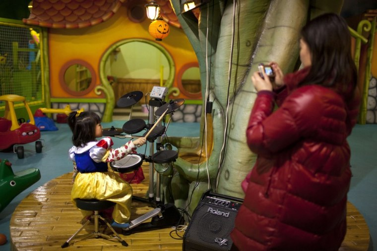A parent takes photos of her daughter playing the drums at a children's play area in a shopping mall in Beijing on Jan. 10.