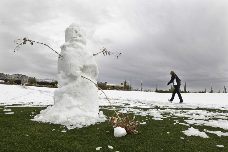 A spectator walks past a snowman made on a fairway after the first round of the Match Play Championship golf tournament was suspended due to snow Wednesday, Feb. 20, in Marana, Ariz.