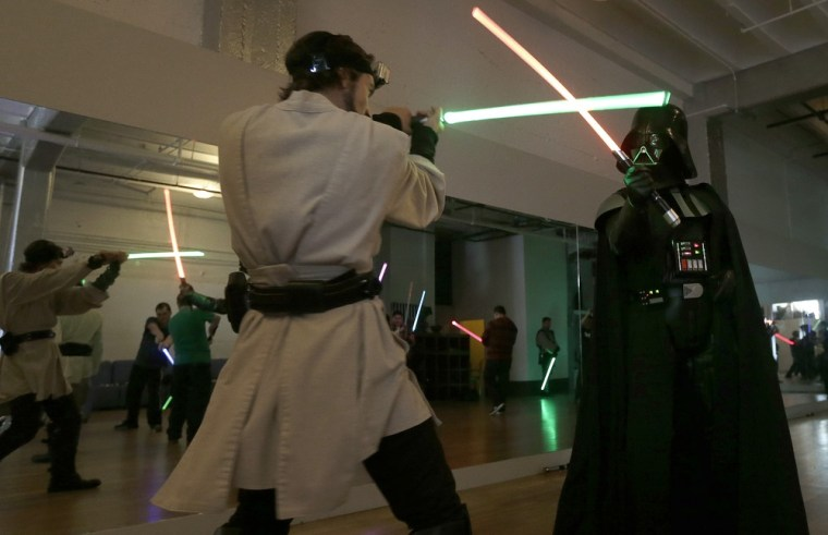 Golden Gate Knights instructor Alain Block and Gary Ripper, dressed as Darth Vader, demonstrate light saber moves during class in San Francisco.