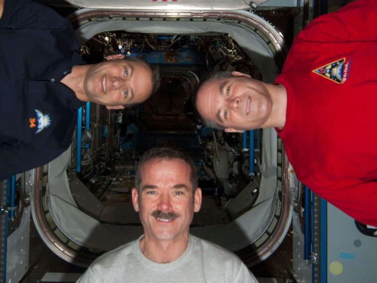 NASA astronaut Tom Marshburn (left), Canadian astronaut Chris Hadfield (center) and space station commander Kevin Ford strike a zero-G pose in the International Space Station's Harmony mode. All three will participate in Friday's Google  Hangout.