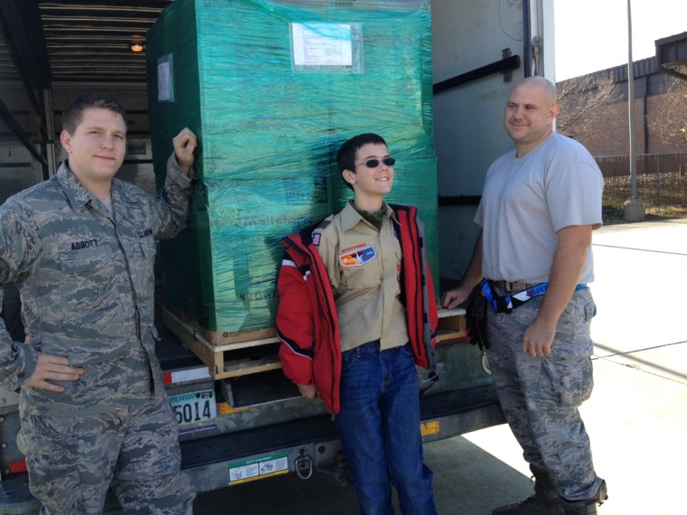 John Ferry stands alongside the truck loaded with clothes bound for Afghanistan in Andrews Air Force Base.