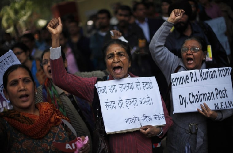 Protesters near the Indian parliament Thursday complain that a new sexual violence law is inadequate. Their signs call for the removal of the deputy chairman of the parliament's upper house, P.J. Kurien, who is facing rape allegations.