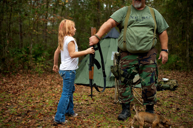 Brianna, 9, of the North Florida Survival Group hands an AK-47 rifle to Jim Foster, 57, the group's leader, before heading out to conduct enemy contact drills.