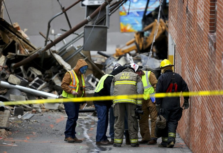 Investigators look down a hole in an alley near JJ's Restaurant after an explosion destroyed the establishment Tuesday, Feb. 19, in Kansas City, Mo.