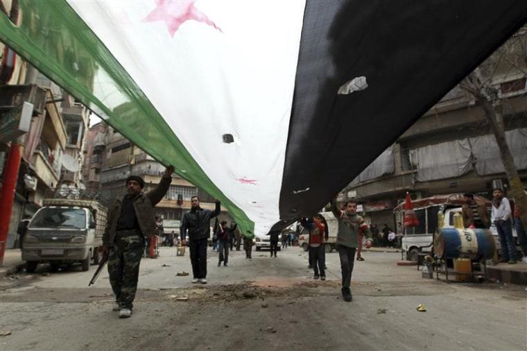 Demonstrators hold a giant opposition flag during a protest against Syria's President Bashar Assad in Bustan al-Qasr district in Aleppo, Feb. 22, 2013. REUTERS/Muzaffar Salman