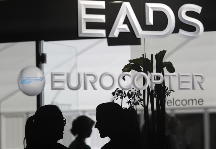 Visitors talk near the welcome desk of the EADS booth at the ILA Berlin Air Show in Selchow near Schoenefeld south of Berlin on September 13, 2012. RE...