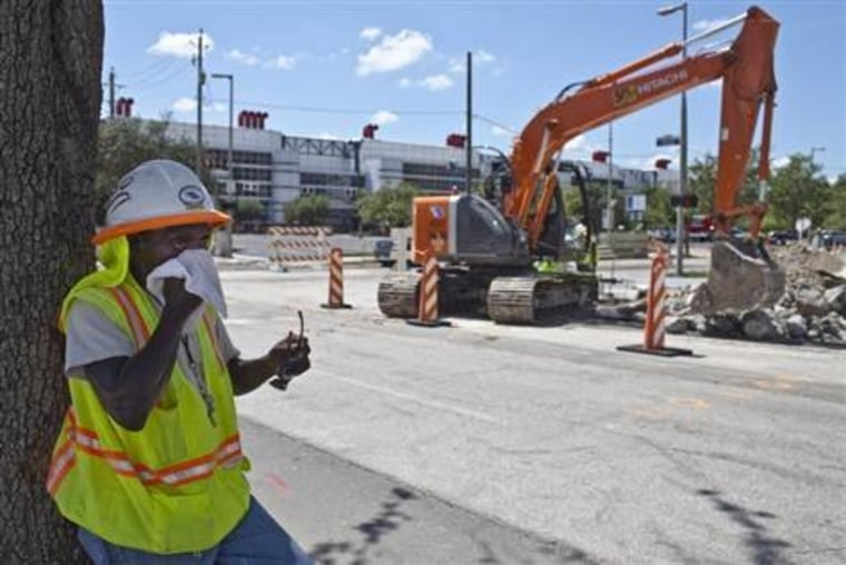 In this file photo, construction worker Chester Gibson wipes sweat from his face on a hot day in Houston, Tex.