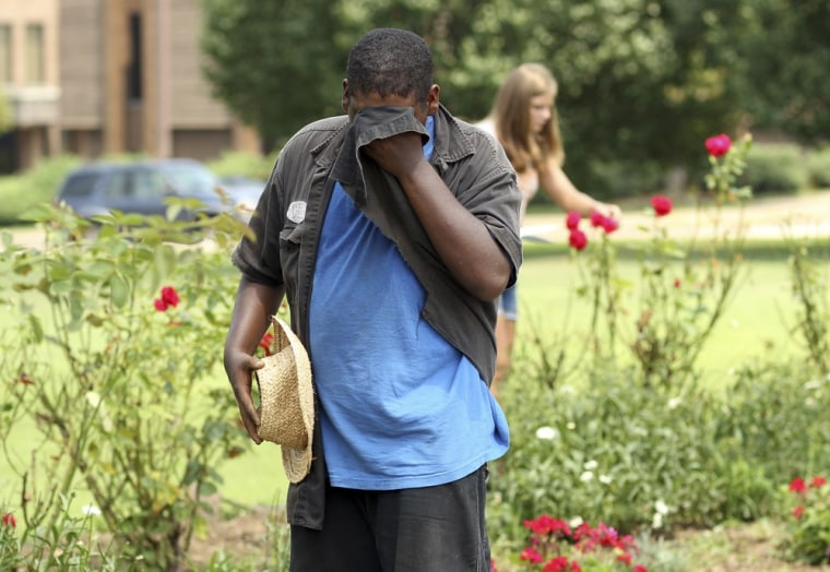 In this Thursday, July 21, 2011 photo, Patrick Nelson wipes the sweat from his face while working on a project for Huntington Community Gardens as temperatures reach over 90 degrees in Huntington, W. Va.