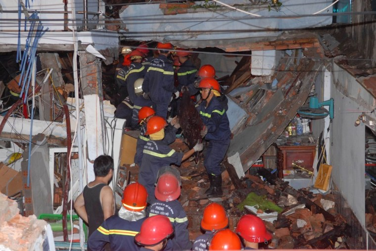Rescuers search for victims at a damaged warehouse in Vietnam's southern Ho Chi Minh city in this picture provided by Vietnam News Agency February 24, 2013. Twin blasts at a warehouse owned by a cinema special effects expert killed 10 people and reduced three homes to burning rubble in Vietnam's biggest city, state media reported on Sunday.