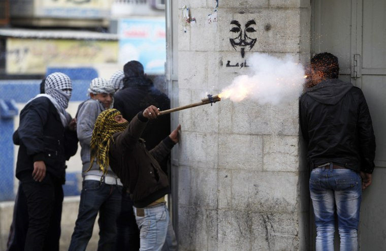A Palestinian protester uses a makeshift launcher to shoot fire crackers as another protester takes cover during clashes with Israeli soldiers and border policemen in the West Bank city of Hebron, Feb. 24. Israel on Sunday demanded the Palestinian Authority stem a surge of anti-Israeli protests ahead of U.S. President Barack Obama's visit to the region next month. The death in an Israeli jail of a Palestinian detainee on Saturday and an on-going hunger strike by four inmates have fueled tensions in the West Bank.