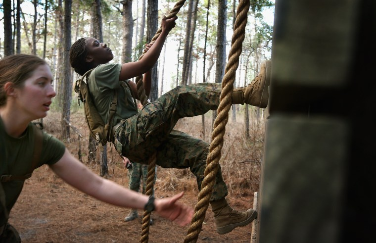 Pfc. Michaela Walker and Pfc. Britney James climb an obstacle on the Endurance Course.