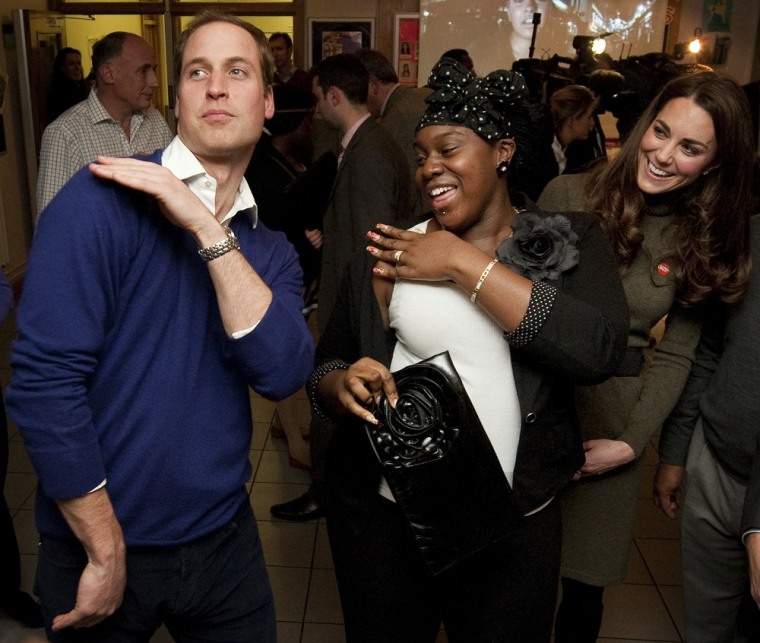 Prince William, Duke of Cambridge dances with Vanessa Boateng as his wife Catherine, Duchess of Cambridge looks on during a reception at Centrepoint's Camberwell Foyer on December 21 in London, England.