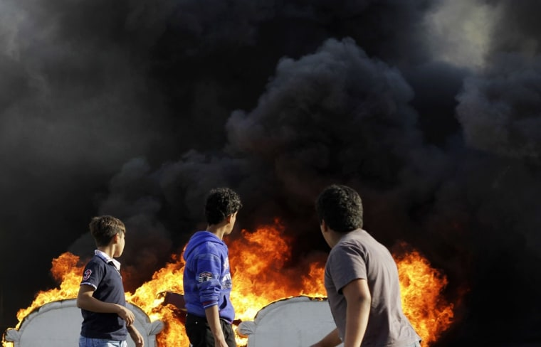 Bahraini boys look at an anti-government protester, unseen, as he adds fuel to old furniture being set on fire in a street in Malkiya on Feb. 26, 2013.