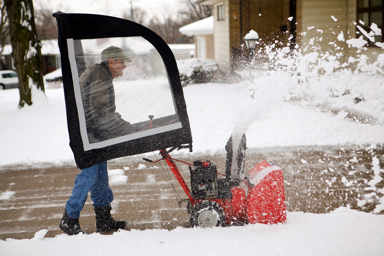 Lloyd Anderson, 88, uses a snowblower with a canopy to clear his driveway on Lover's Lane in St. Joseph, Mo., on Feb. 26. A major winter storm paralyzed parts of the nation's midsection Tuesday, dumping a fresh layer of heavy, wet snow atop cities still choked with piles from the previous system and making travel perilous from the Oklahoma Panhandle to the Great Lakes.
