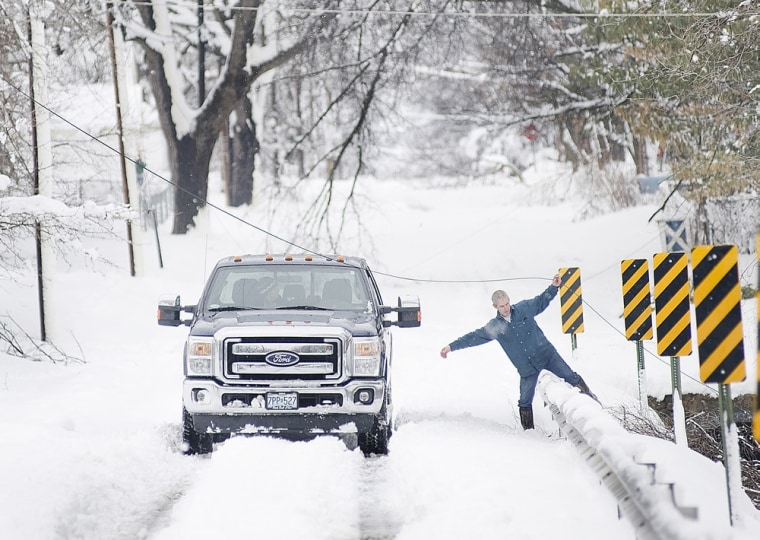 Tedd Hendrix, of Sedalia, Mo., frees a line of cable from downed branches Tuesday as he works to tie the line off so that it is elevated and out of the road. A snow storm, the second in less than a week, dumped about a foot of snow in Sedalia, knocking out power around the town and collapsing the roofs of several buildings.