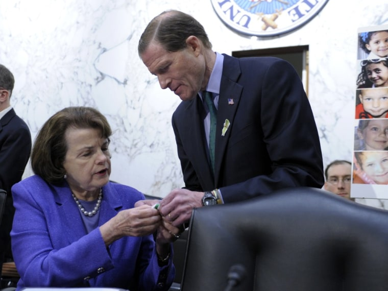 Senate Judiciary Committee member Sen. Dianne Feinstein, D-Calif., gets help with a green ribbon pin for the victims of Sandy Hook Elementary School, from fellow committee member Sen. Richard Blumenthal, D-Conn., on Capitol Hill in Washington, Wednesday, Feb. 27, 2013.