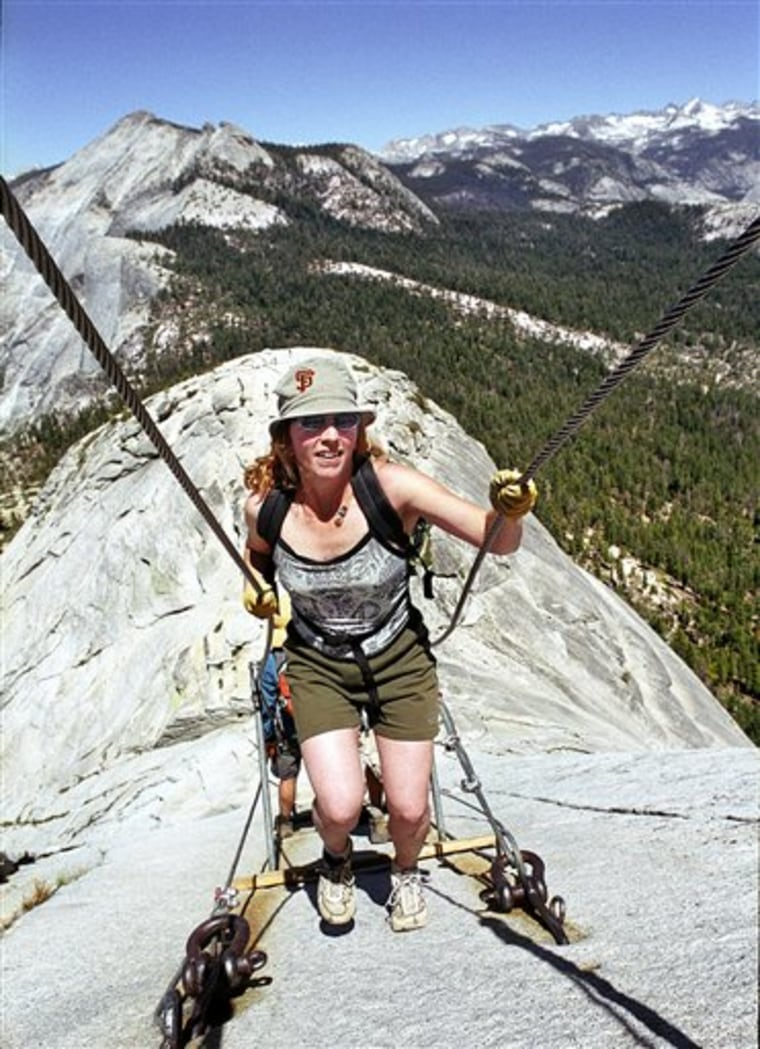 In this file photo, Thea Roberts, of Oakland, Calif., pulls herself up the cable route on the way to the summit of Half Dome.