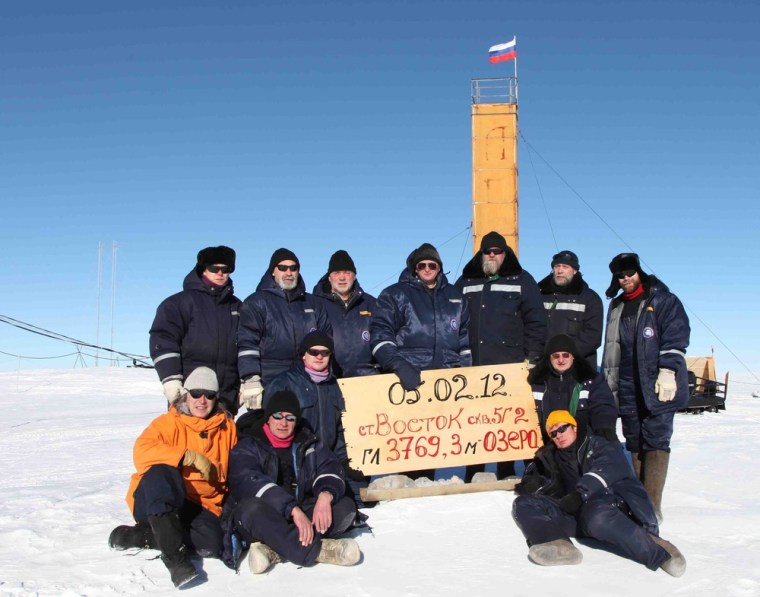 Russian researchers at the Vostok station in Antarctica pose for a picture after reaching Lake Vostok in February 2012. Scientists hold a sign reading