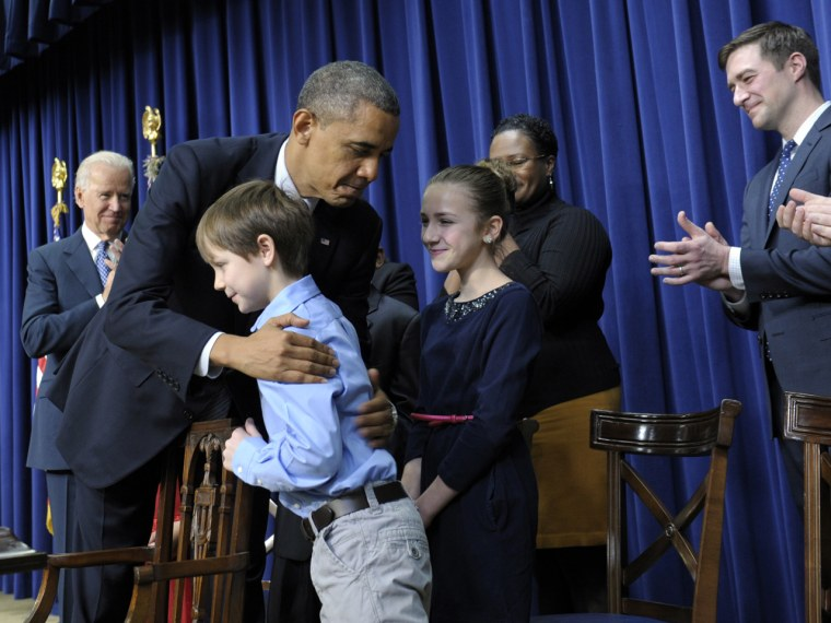 President Barack Obama, accompanied by Vice President Joe Biden, left, hugs 8-year-old letter writer Grant Fritz during a news conference on proposals to reduce gun violence, Wednesday, Jan. 16, 2013, in the South Court Auditorium at the White House in Washington. Obama and Biden were joined by law enforcement officials, lawmakers and children who wrote the president about gun violence following the shooting at an elementary school in Newtown, Conn., last month.