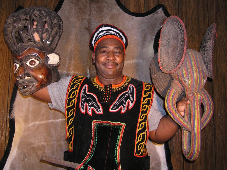 African-American genealogist William Holland, dressed in traditional garb, shows off the ceremonial masks he bought on eBay. He plans to return the masks to the tribes from whence they came during a trip to Cameroon this month.