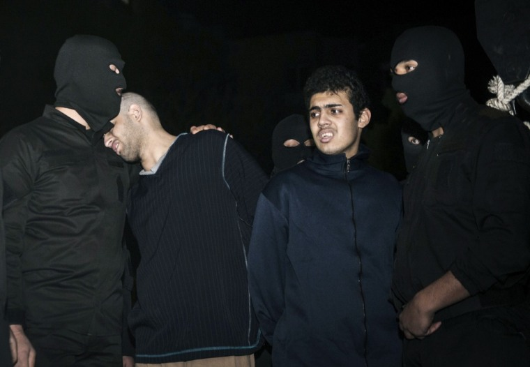 """Alireza Mafiha, second left, leans his head on the shoulder of a security officer moments before his execution along with Mohammad Ali Sarvari, second right, in Tehran, Iran, on Jan. 20, 2013. Iran publicly executed two men on Sunday after posting a video on YouTube in December 2012 showing them robbing and assaulting a man with a machete on a street in Tehran. Judiciary chief Ayatollah Sadeq Larijani called it a """"moharebeh"""" crime, which Iran's legal code defines as """"defiance of God"""", or the state, and is punishable by hanging."""