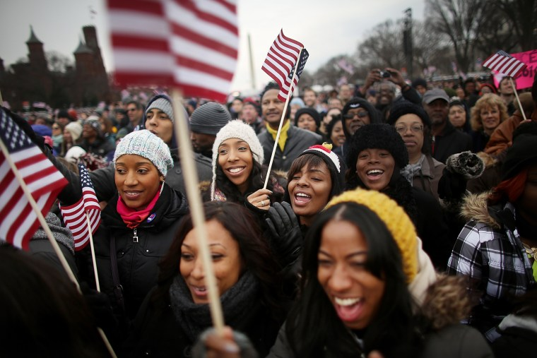 Revelers celebrate in front of the Washington Monument near the U.S. Capitol building on the National Mall while attending the public inauguration ceremony on Jan. 21 in Washington, D.C.