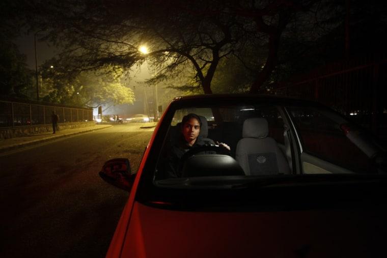 Chandani sits inside her car on a street in New Delhi.
