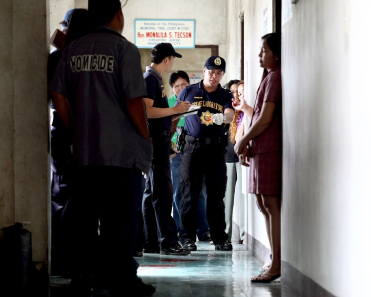 Police examine the scene where prosecutor Maria Teresa Casino was wounded at the Regional Trial Court building in Cebu city in central Philippines on Tuesday.