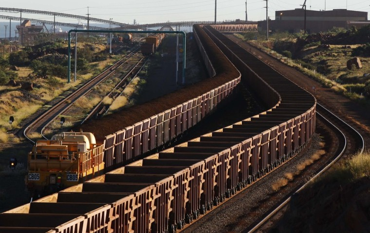 A train loaded with iron ore travels toward the Rio Tinto Parker Point iron ore facility as an empty train leaves, in Dampier in the Pilbara region of western Australia, in this file picture taken April 20, 2011.