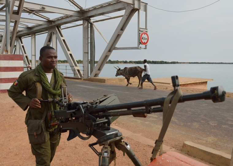 A Malian soldier holds a machine gun as he stands guard at the entrance of a strategic bridge over the Niger river on Jan. 22, 2013, near Markala, north of Bamako. Mali's army chief today said his French-backed forces could reclaim the northern towns of Gao and fabled Timbuktu from Islamists in a month, as the United States began airlifting French troops to Mali.