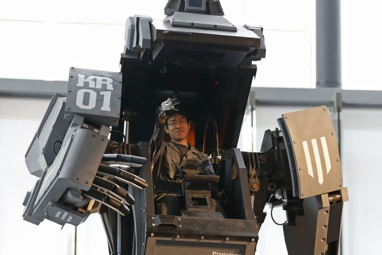 Robotics expert Watanaru Yoshizaki demonstrates how to operate the arm of a giant