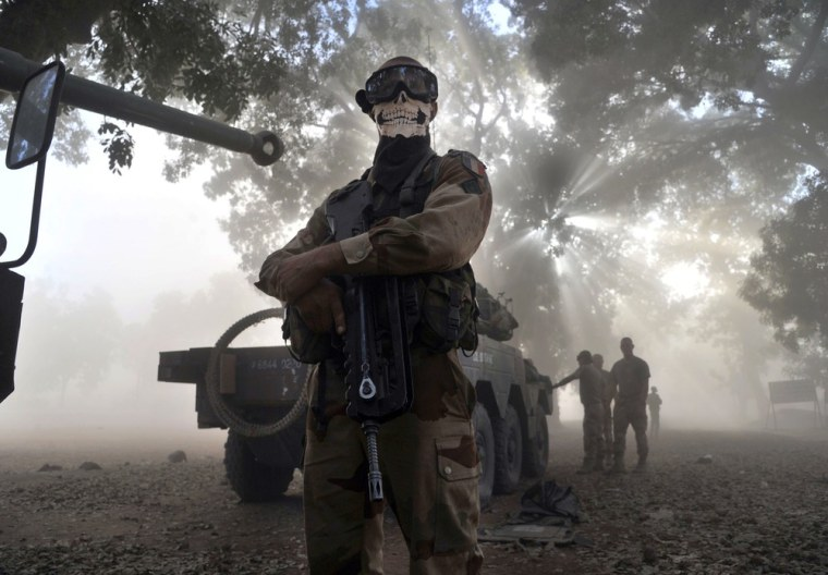 A French soldier wearing a skeleton mask stands next to a tank in a street in Niono, Mali.