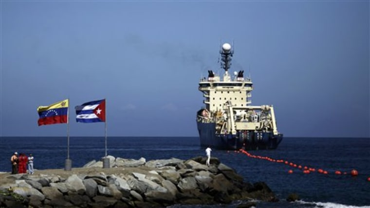 FILE - In this Jan. 22, 2011 file photo, people stand on a breakwater, with a Venezuelan flag, left, and a Cuban flag, as a specialized ship rolls out...