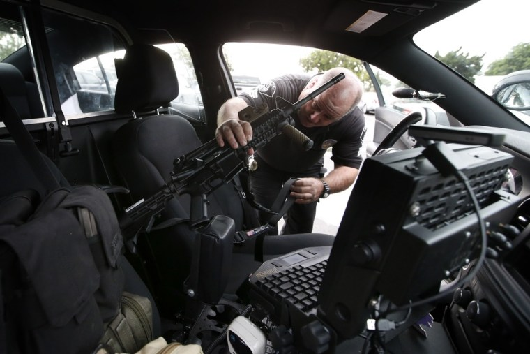 Santa Ana school police Sgt. Kevin Philips locks his rifle in a gun rack mounted in a police vehicle in Santa Ana, Calif., Jan. 24, 2013. The semiautomatic rifles look like they belong in a war zone instead of a suburban public school, but officials in this Los Angeles-area city say the high-powered weapons now in the hands of school police could prevent a massacre.