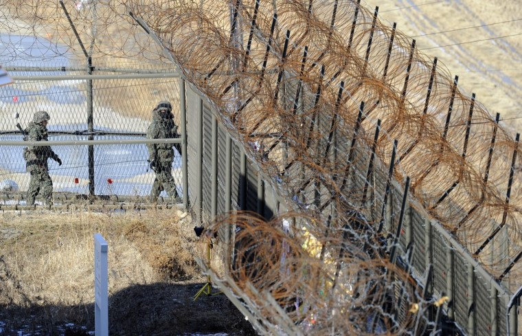 South Korean soldiers patrol along a fence in Paju near the Demilitarized Zone dividing the two Koreas Friday.