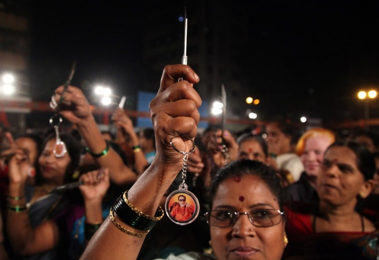 Indian women hold up knives that were distributed by the Shiv Sena party in Mumbai, India, on Wednesday.