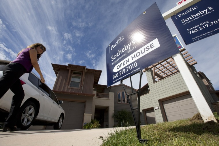 In this Wednesday, Nov. 14, 2012, photo, a woman walks towards a home for sale during a viewing for brokers in Leucadia, Calif.