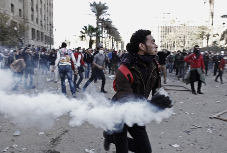 An Egyptian protester runs with a live tear gas canister during clashes with riot police around Cairo's Tahrir Square on Friday.